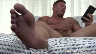 Buff stud masturbates with his big soft feet on full display
