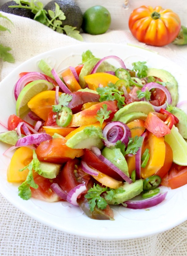 Colorful heirloom tomato avocado salad with purple onions and lime dressing in a white bowl.
