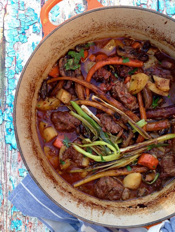 Orange Pot of Italian Beef Stew on a Blue Rustic Table