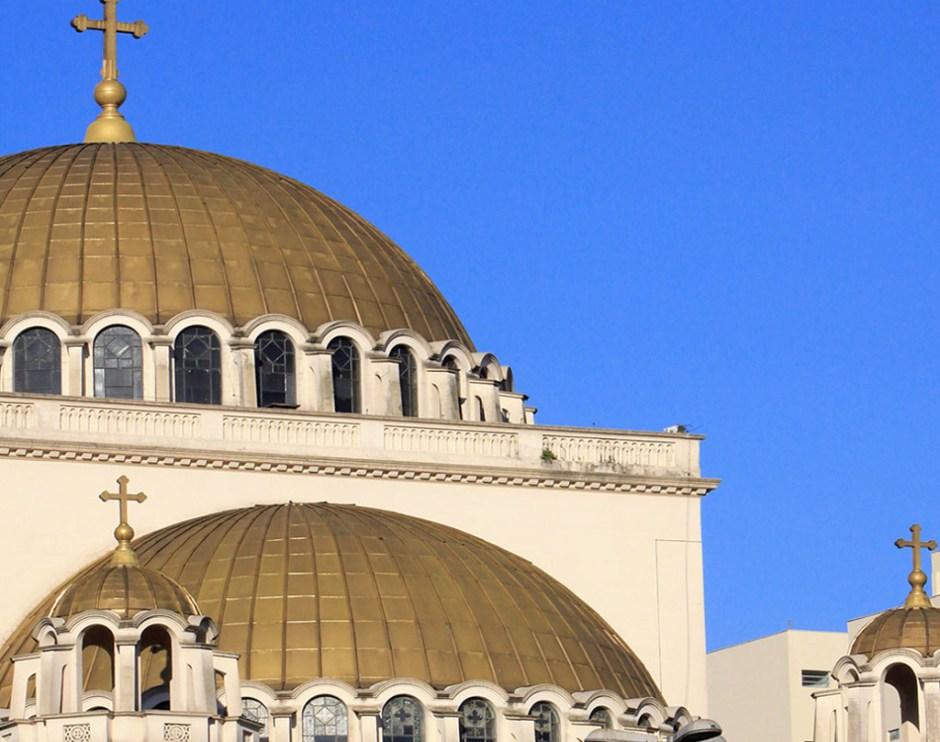 Imagem em close up de 2 domos dourados da Catedral. O de baixo é um meio domo, encostado em uma parede e, na base, é rodeado por diversas janelas de vidro sobre armação metálica e topo arredondado. O domo principal fica acima, tem uma grande cruz no topo e, como o de baixo, também é rodeado por diversas janelas. Tudo sob um céu muito azul sem nuvens.