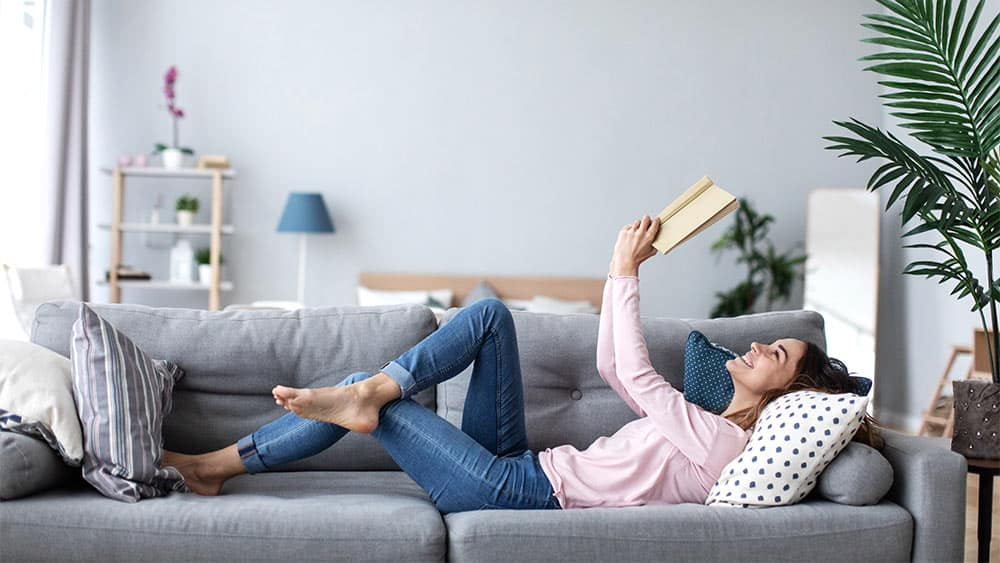 Girl reading a book on the couch.