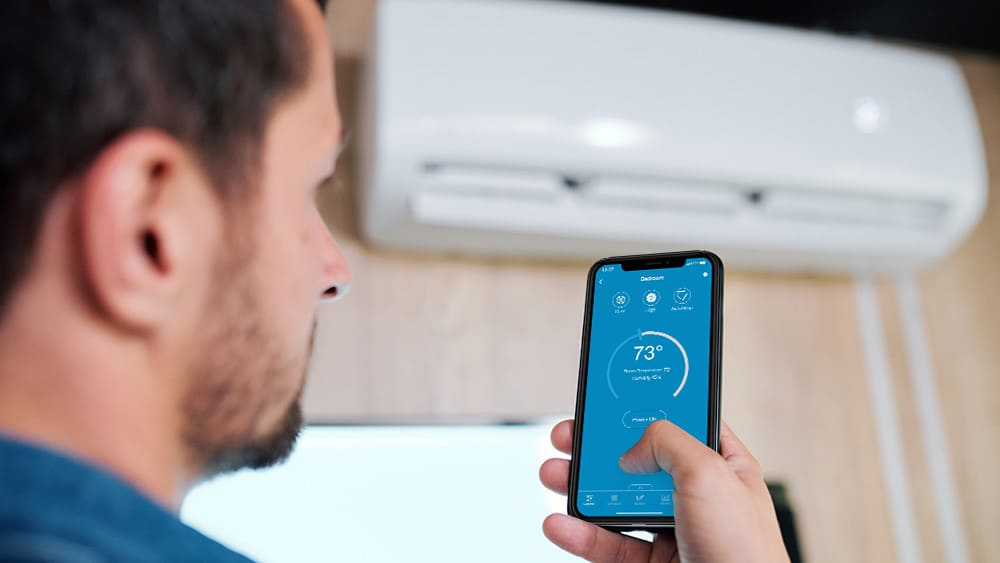 Man using phone to control AC.