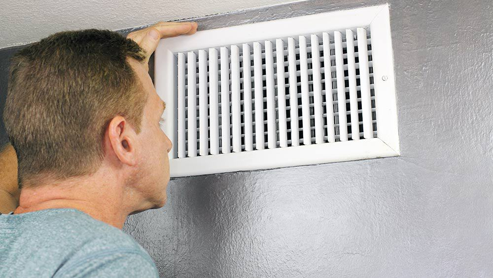 Man checking AC vent.
