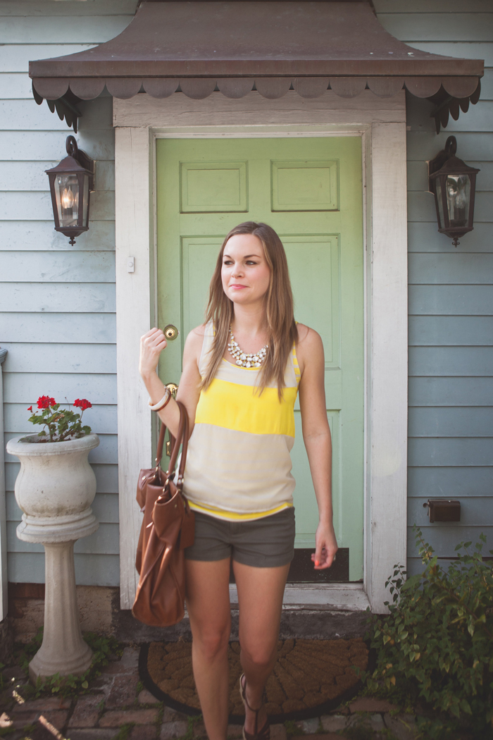 Ciera wearing olive shorts, yellow top and brown leather bag