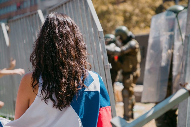 Woman draped in Chilean flag facing riot police behind a barrier.  International Women's Day 2020