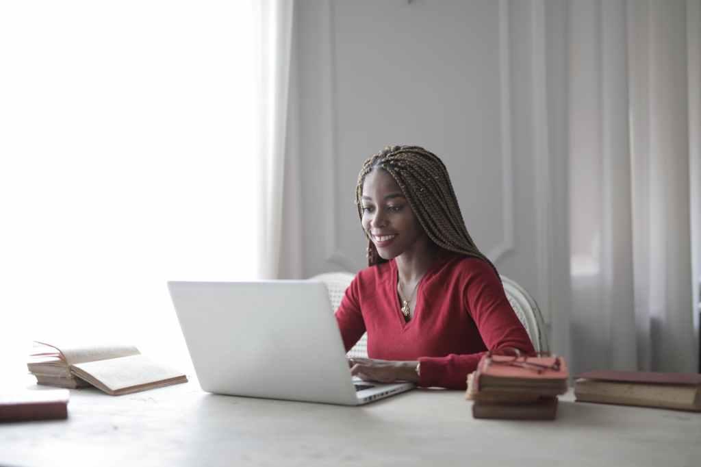 woman in red long sleeve shirt using macbook air