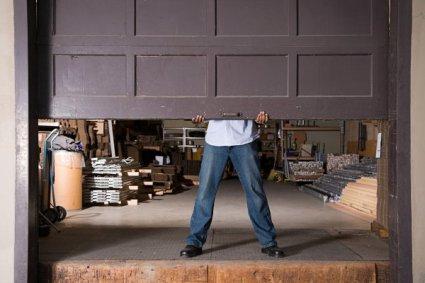 A man opening up a garage door.