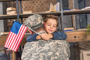 military father and son with usa flag embracing