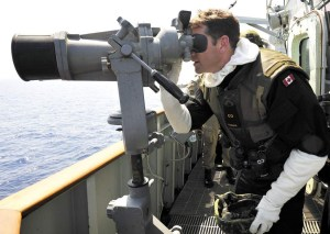 "CDR Craig Skjerpen, commanding officer of HMCS Charlottetown, uses the ""Big Eyes"" binoculars to look for small boats crewed by Libyan pro-regime forces."