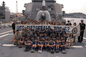 US_Navy_061015-N-5334H-179_USS_Fitzgerald_(DDG_62)_Commanding_Officer,_Cmdr._David_Hughes_and_Executive_Officer,_Lt._Cmdr._John_Tolg_hold_up_the_ship's_banner_with_children_and_adults_from_the_Cub_Scouts_Tokyo_Group
