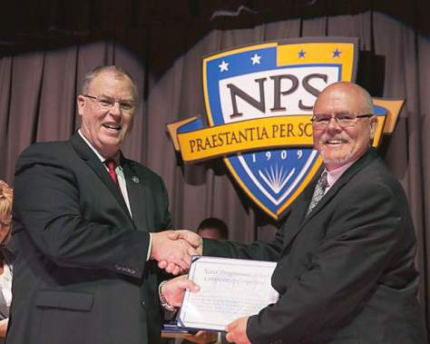 Deputy Secretary of Defense presents a Master of Science diploma to Ken Thomas at the Naval Postgraduate School.