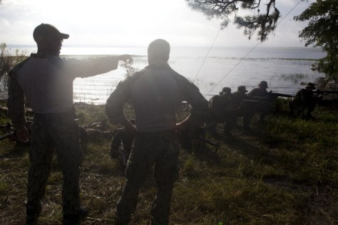 Petty Officers 3rd Class Raymond Delossantos (left) and 2nd Class Jeremy Milford (right) of Riverine Squadron 3 instruct Paraguayan Marines on establishing security after debarking riverine craft during UNITAS 2012. Credit: Cpl Tyler Thornhill, USMC
