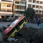 """Visioni inusuali: un autobus """"affonda"""" in un cratere in mezzo alla strada"""