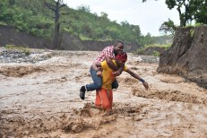 A man is carried across the river La Digue in Petit Goave where the bridge collapsed during the rains of the Hurricane Matthew, southwest of Port-au-Prince, October 5, 2016. Haiti and the eastern tip of Cuba -- blasted by Matthew on October 4, 2016 -- began the messy and probably grim task of assessing the storm's toll. Matthew hit them as a Category Four hurricane but has since been downgraded to three, on a scale of five, by the US National Hurricane Center. / AFP PHOTO / HECTOR RETAMAL