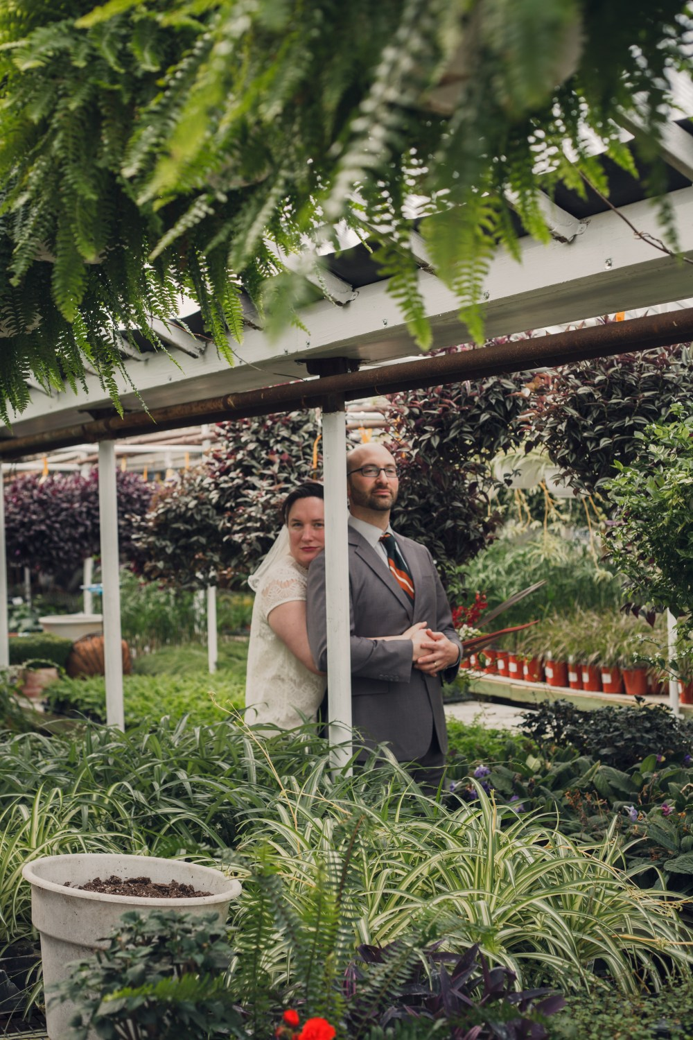 wedding couple holding each other in greenhouse