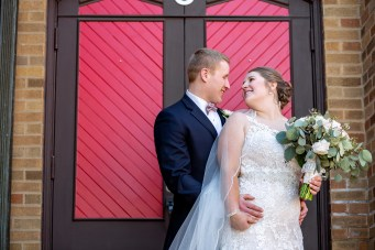 just married couple in front of red door