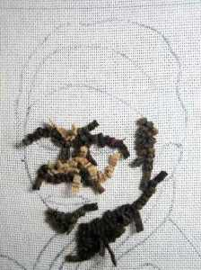 Rug hooking in the dark values of a face