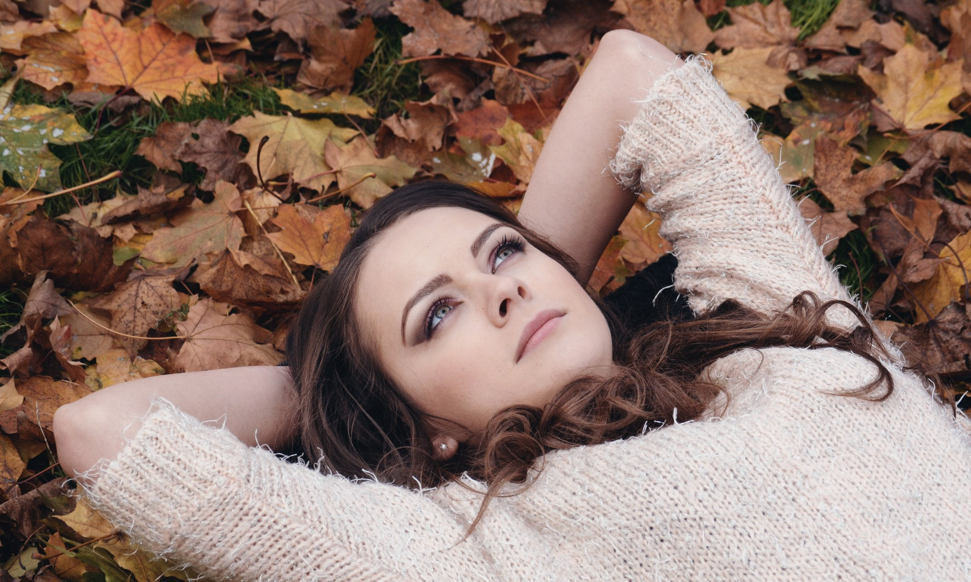 woman lying on leaves looking up at sky as if thinking
