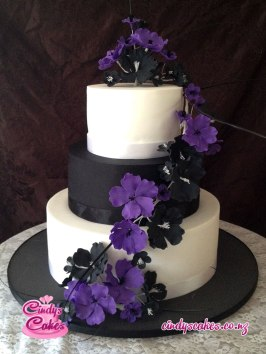 3 tier black and white wedding cake decorated with purple and black flowers