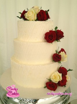 3 tier Buttercream wedding cake decorated with red and yellow roses