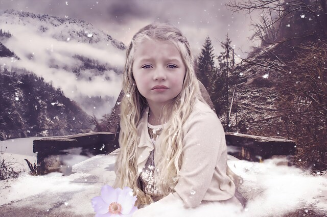 A little girl with blonde hair outside in the cold looking sad.