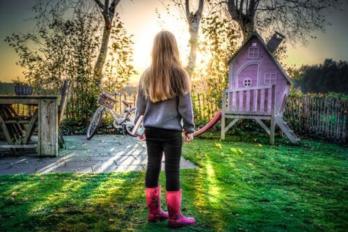 A girl with long blonde hair standing in front of a playhouse.