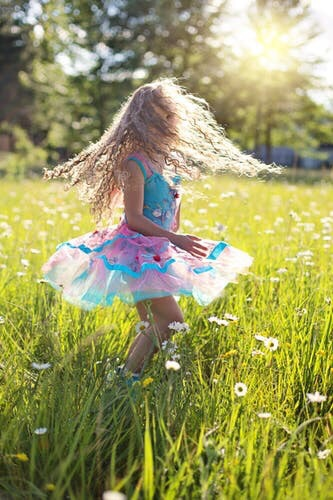 Girl with long blonde hair twirling in a field.