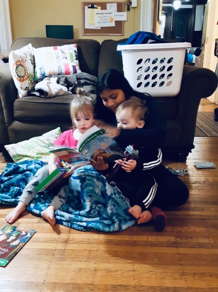 A woman reading a book to Katy's two children.