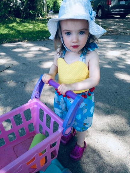 Katy's daughter pushing a toy grocery cart.