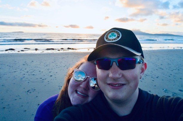 Emily and Matthias with a beach and sunset behind them.