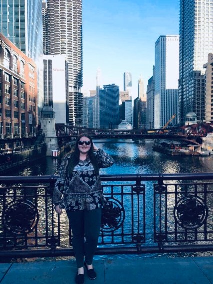 Emily standing in front of large city buildings on a river.