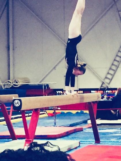 Jaelyn doing a handstand on a balance beam.