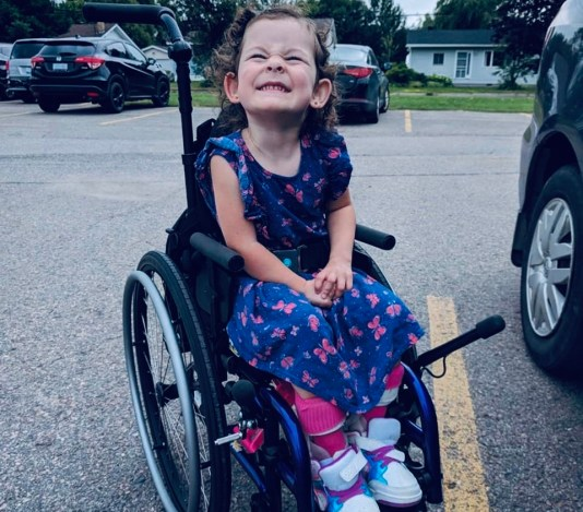 Ellie smiling big as she sits in her wheelchair.