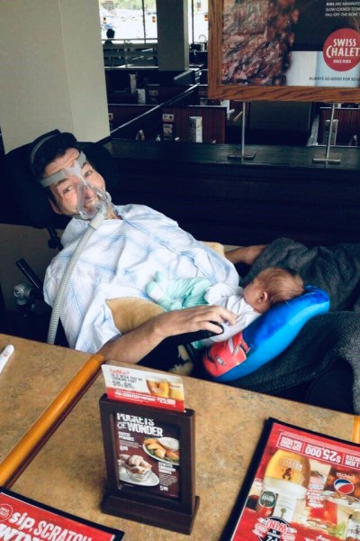 A man in a wheelchair holding his grandson.