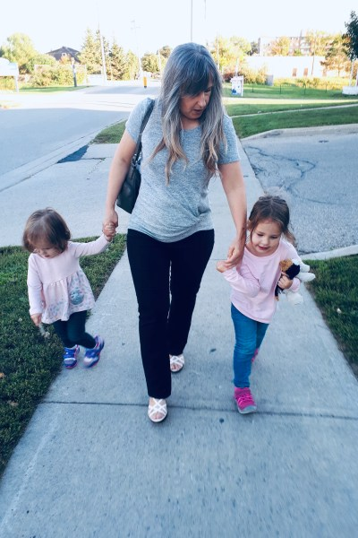 A grandmother walking down the sidewalk with her two granddaughters.