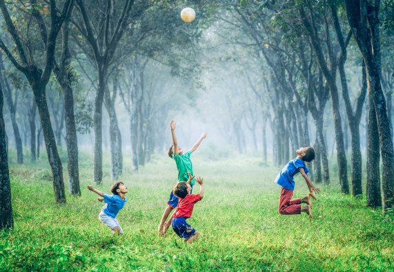 four children playing with a soccer ball