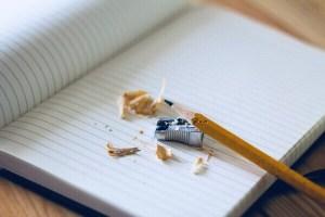 a school book, pencil and pencil sharpener