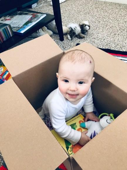 Aubrey sitting in a box, smiling.