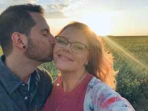 Dave kissing Katelyn's cheek. They are standing in a field with a sunrise behind them.