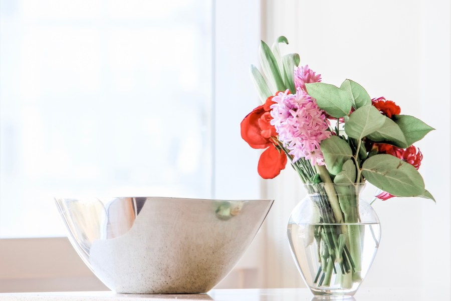 vase of flowers with shimmering bowl on a table