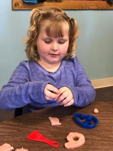 Child cutting playdoh with cookie cutters.
