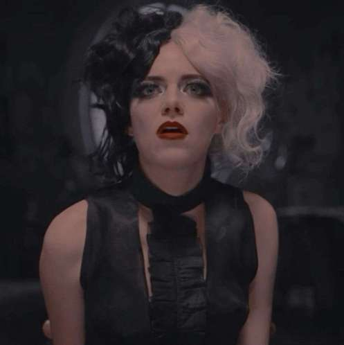 Plano medio corto de Emma Stone personificando a Cruella De vil con el pelo bicolor.