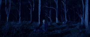 A woman sits alone in a dark forest.