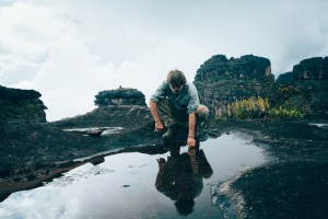 A man bends over to touch a puddle of water among rock formations. His reflection is seen on the glossy water.