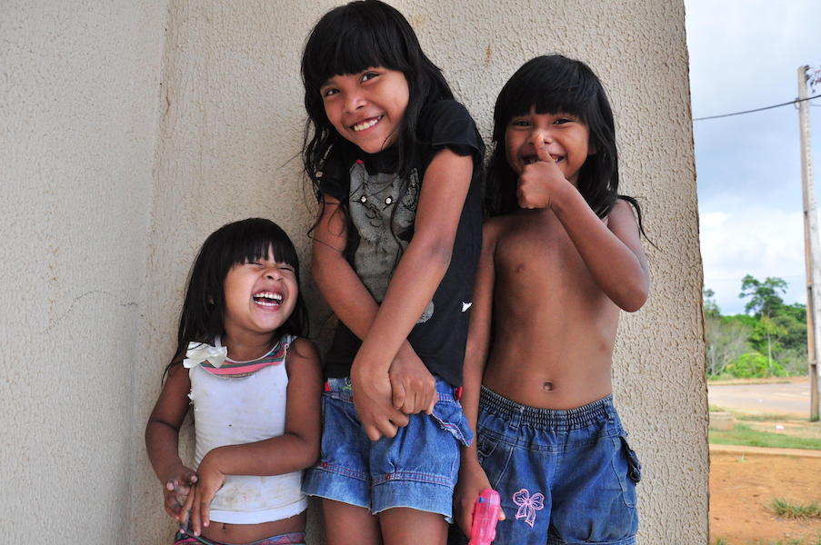 Three children with long black hair and bangs are shy but giggling.