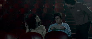 A theatre attended speaks to woman smoking a cigarette. Man next to woman is looking down at program.