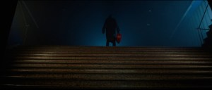 A dark figure stands at the top of a set of stairs.
