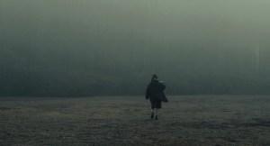 Woman walks away in the foggy distance.