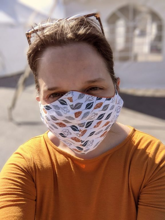 Aili, wearing a mask, standing outside of VDH tents at an outdoor mass vaccination site.