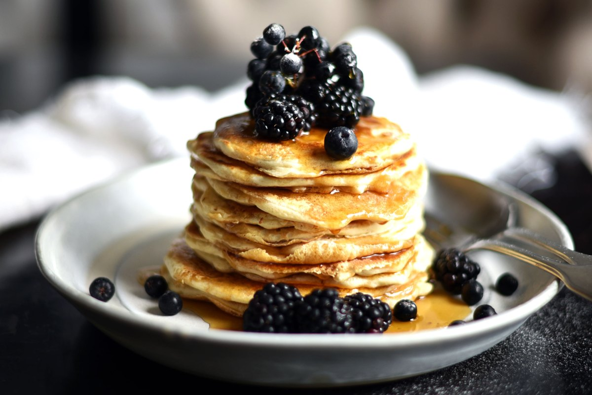 Pancakes with blackberries and blueberries and maple syrup for a healthy and nutrias breakfast